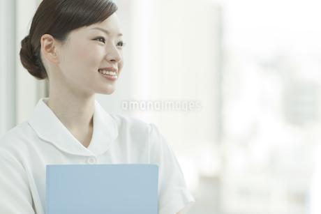 窓辺でファイルを持つ笑顔の看護士の写真素材 [FYI01621285]