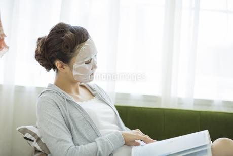 マスクペーパーを顔につけ雑誌を読む女性の写真素材 [FYI01621291]
