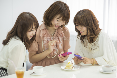 スマートフォンを見せて微笑む3人の若い女性の写真素材 [FYI01621293]