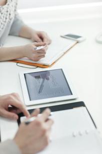 タブレットPCで打ち合わせをするビジネスマンとビジネスウーマンの写真素材 [FYI01621309]