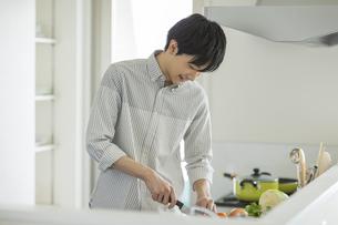 キッチンで野菜を切る若い男性の写真素材 [FYI01621317]