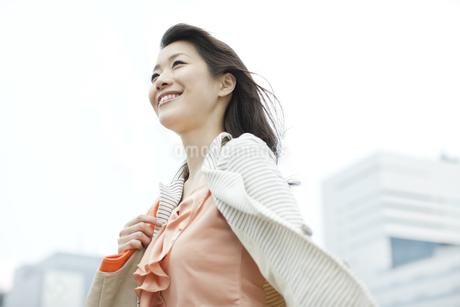 オフィス街を歩く笑顔のビジネスウーマンの写真素材 [FYI01621319]