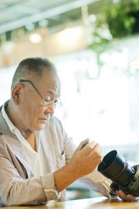 一眼レフカメラを持つシニア男性の写真素材 [FYI01621337]