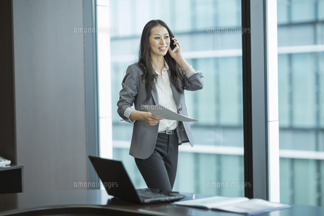 歩きながらスマートフォンで通話するビジネスウーマンの写真素材 [FYI01621341]
