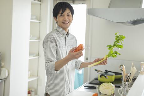 キッチンで野菜を持つ笑顔の若い男性の写真素材 [FYI01621356]
