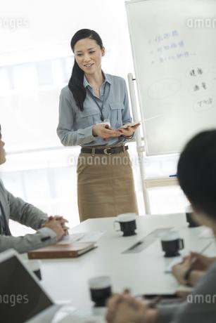 ホワイトボードの前で話すビジネスウーマンの写真素材 [FYI01621362]