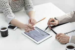 タブレットPCで打ち合わせをするビジネスマンとビジネスウーマンの写真素材 [FYI01621374]