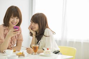 スマートフォンを見せて微笑む2人の若い女性の写真素材 [FYI01621385]