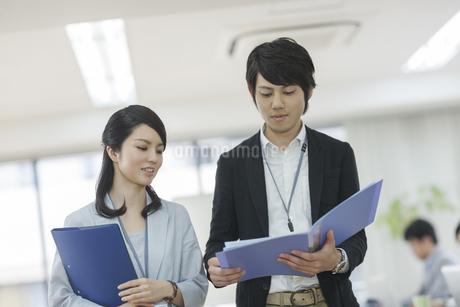 ファイルを見て話すビジネスマンとビジネスウーマンの写真素材 [FYI01621393]