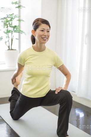 室内でストレッチをする笑顔の中高年女性の写真素材 [FYI01621397]
