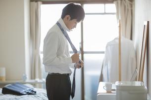 自宅でネクタイを結ぶフレッシュマンの写真素材 [FYI01621429]