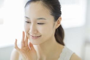 指で頬に触れ潤いを実感し微笑むスキンケアイメージの写真素材 [FYI01621486]