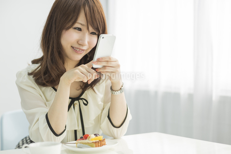 スマートフォンを持ち微笑む若い女性の写真素材 [FYI01621491]
