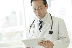 タブレットPCを操作する男性医師の写真素材 [FYI01621492]