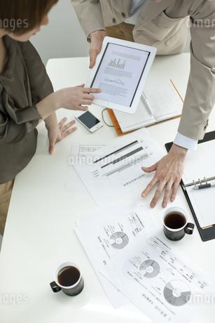 タブレットPCで打ち合せするビジネスマンとビジネスウーマンの写真素材 [FYI01621495]