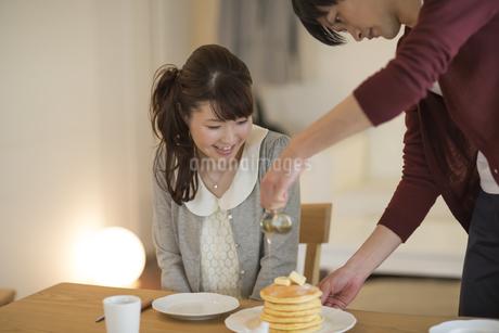 パンケーキにシロップをかける若い男性の写真素材 [FYI01621497]