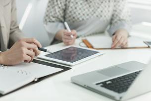 タブレットPCで打ち合わせをするビジネスマンとビジネスウーマンの写真素材 [FYI01621513]
