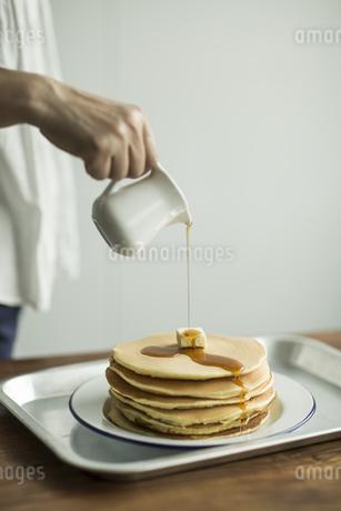 パンケーキにシロップをかける女性の写真素材 [FYI01621514]
