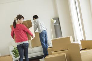 引っ越しのダンボールを運ぶ若いカップルの写真素材 [FYI01621523]