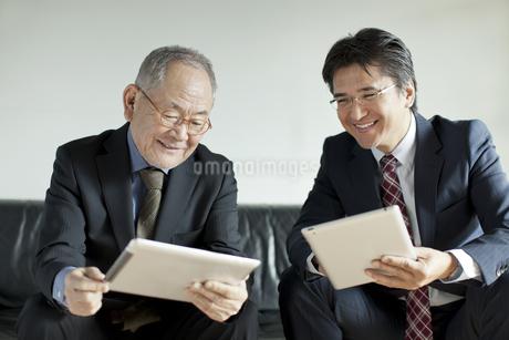 タブレットPCを操作する2人のビジネスマンの写真素材 [FYI01621535]