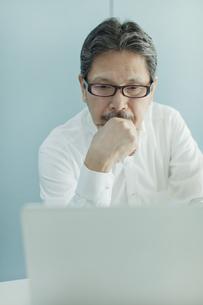 パソコンの前で考えるシニア男性の写真素材 [FYI01621544]