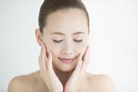 頬に手をあてる女性のスキンケアイメージの写真素材 [FYI01621560]