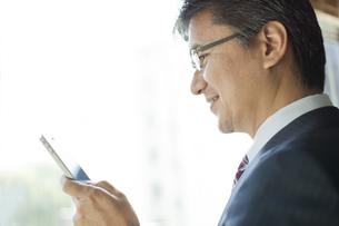 スマートフォンを操作するビジネスマンの写真素材 [FYI01621562]
