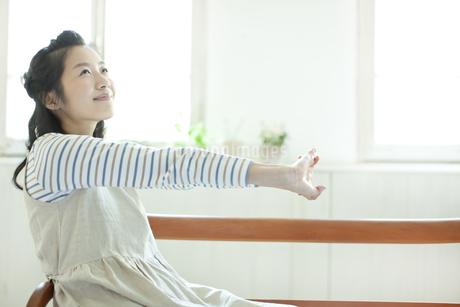 座って身体を伸ばす若い女性の写真素材 [FYI01621571]