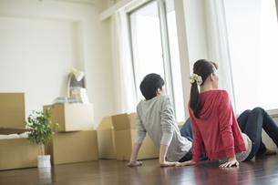 床に座り外を眺める若いカップルの後ろ姿の写真素材 [FYI01621578]