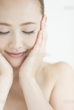 両手で顔を包み込む女性のスキンケアイメージの写真素材 [FYI01621583]
