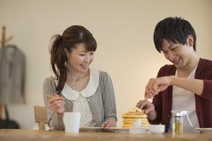 パンケーキをカットする若い男性と笑顔の若い女性の写真素材 [FYI01621585]
