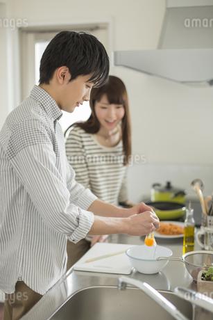 卵を割る若い男性と見ている若い女性の写真素材 [FYI01621587]