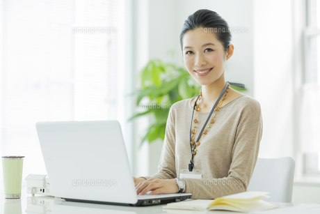 パソコンをする笑顔のビジネスウーマンの写真素材 [FYI01621588]