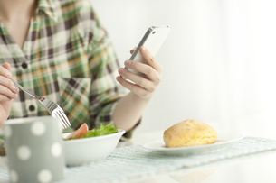 スマートフォンを操作しながら朝食を食べる若い女性の写真素材 [FYI01621591]