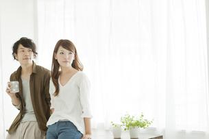 テーブルに腰をかける若い夫婦の写真素材 [FYI01621601]