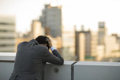 屋上で頭を抱えるビジネスマンの後姿の写真素材 [FYI01621606]
