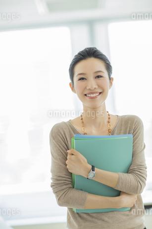 ファイルを持つ笑顔のビジネスウーマンの写真素材 [FYI01621608]