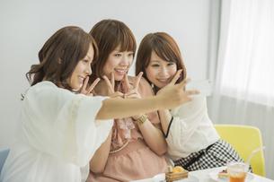 スマートフォンで撮影をする3人の若い女性の写真素材 [FYI01621609]