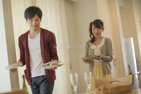 夕食の料理を運ぶ若いカップルの写真素材 [FYI01621611]