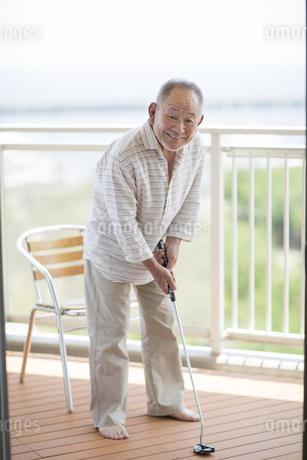 バルコニーでゴルフの練習をするシニア男性の写真素材 [FYI01621616]
