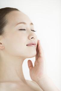 頬に手をあてる女性のスキンケアイメージの写真素材 [FYI01621628]