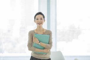ファイルを持つ笑顔のビジネスウーマンの写真素材 [FYI01621632]