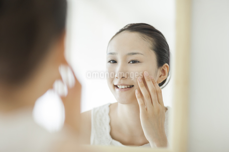 鏡を見て顔に手を触れるスキンケアイメージの写真素材 [FYI01621633]