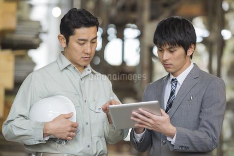 タブレットPCで打ち合わせする男性社員の写真素材 [FYI01621638]