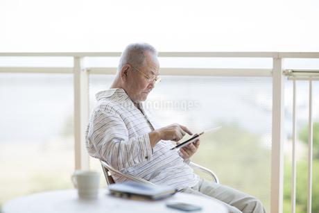 バルコニーでタブレットPCを操作するシニア男性の写真素材 [FYI01621641]