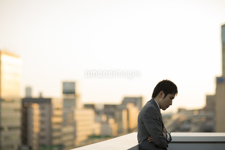 屋上で腕組みをして悩むビジネスマンの写真素材 [FYI01621644]