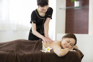 背中のオイルマッサージを受ける若い女性の写真素材 [FYI01621647]
