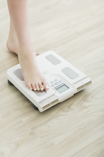 体重計に乗る女性の足元の写真素材 [FYI01621648]