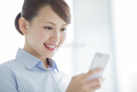 スマートフォンを見るビジネスウーマンの写真素材 [FYI01621653]
