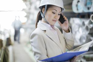 スマートフォンで通話する女性社員の写真素材 [FYI01621657]